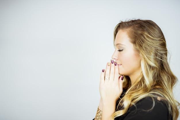 Zijprofiel van een biddende blonde vrouw tegen een wit