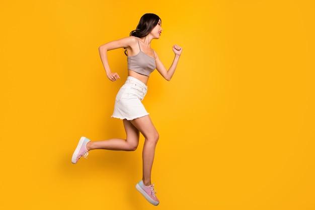 Zijprofiel volledige lengte lichaamsgrootte foto van vrolijke positieve schattige mooie vriendin rennen naar springende verkoop geïsoleerde levendige kleuren achtergrond