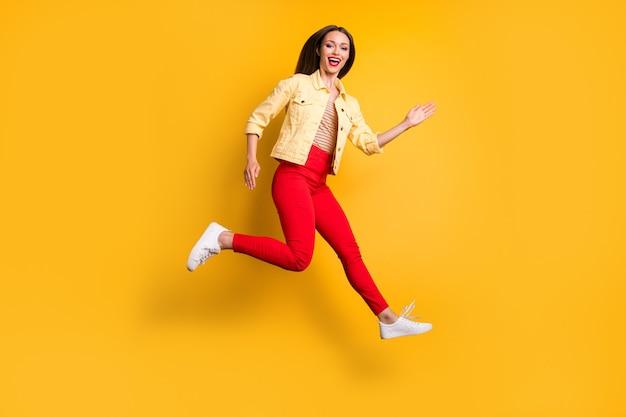 Zijprofiel volledige lengte lichaamsgrootte vrolijk vrij schattig charmant meisje rent naar winkelcentrum voor verkoop in rode broek geïsoleerde levendige kleurenmuur