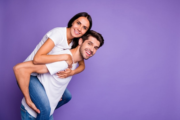 Zijprofielfoto van schattige leuke charmante paar bruinharige mensen met een man die op de rug vrouw glimlach toothy draagt ?? in de buurt van lege witte t-shirt geïsoleerde pastel violette kleur achtergrond