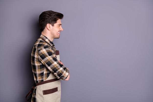 Zijprofielfoto van vrolijke brede stralende man met gekruiste armen op zoek naar lege ruimte geïsoleerde grijze kleur muur