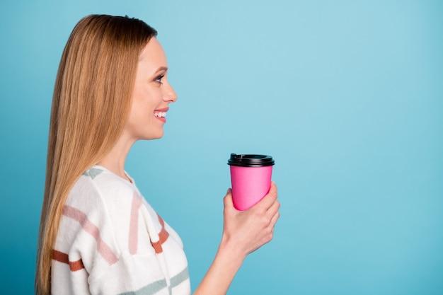 Zijprofielfoto van vrolijke positieve vriendin glimlachend toothily op zoek naar lege ruimte met kopje thee geïsoleerde pastel kleur blauwe muur