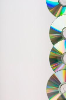 Zijrand met compact discs op witte achtergrond wordt gemaakt die
