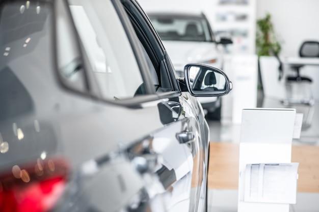 Zijspiegel. zijspiegel op nieuwe personenauto, die het interieur van de auto weerspiegelt die bij de dealer staat;