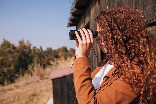 Zijwaarts gekrulde roodharige vrouw kijkt door een verrekijker