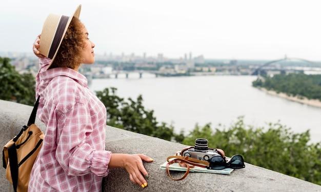Zijwaarts gekrulde vrouw die van het uitzicht geniet