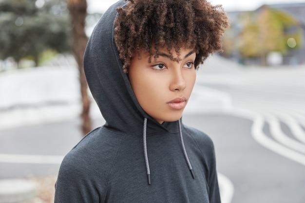 Zijwaarts geschoten van bedachtzame vrouw met donkere huid, krullend haar, draagt hoodie