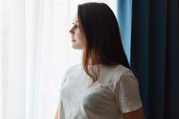 Zijwaarts geschoten van doordachte donkerharige vrouw gekleed in wit t-shirt, denkt aan iets terwijl staat bij raam