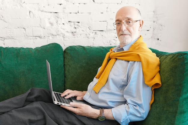 Zijwaarts horizontaal portret van zestig-jarige bebaarde man ondernemer in bril en trui over blauw shirt op afstand werken, zittend op de bank met elektronisch apparaat op zijn schoot, camera kijken