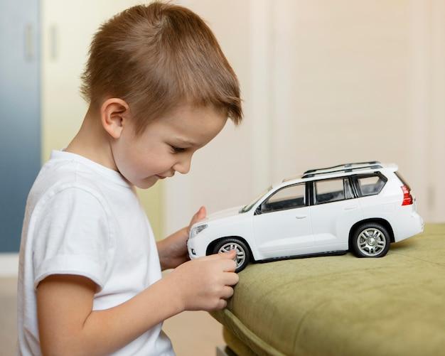 Zijwaarts jongen speelt met een witte auto