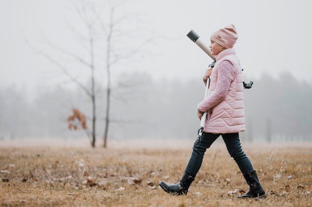 Zijwaarts kind met een telescoop buiten