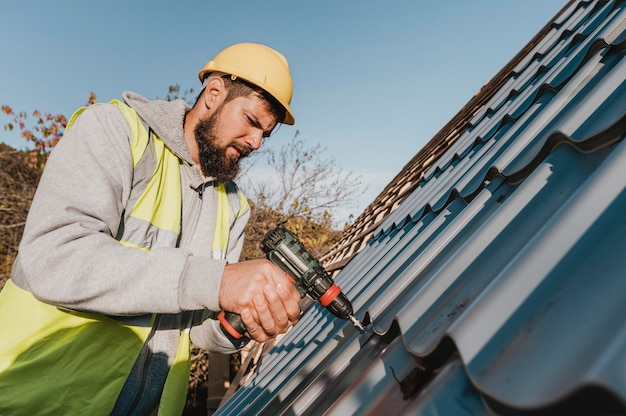 Zijwaarts man aan het werk op dak met een boormachine