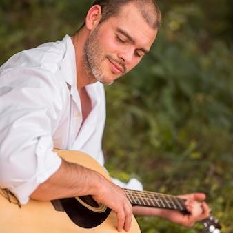 Zijwaarts man gitaarspelen in de natuur
