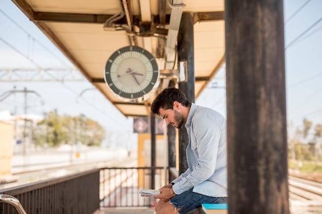 Zijwaarts man wacht op trein