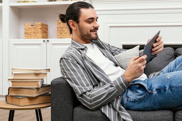 Zijwaarts man zittend op de bank met een tablet