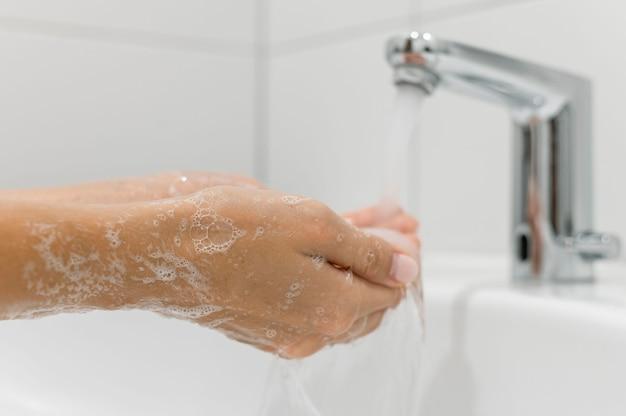 Zijwaarts persoon die handen wast