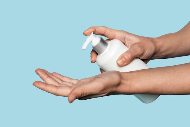Zijwaarts persoon handen wassen geïsoleerd op blauw