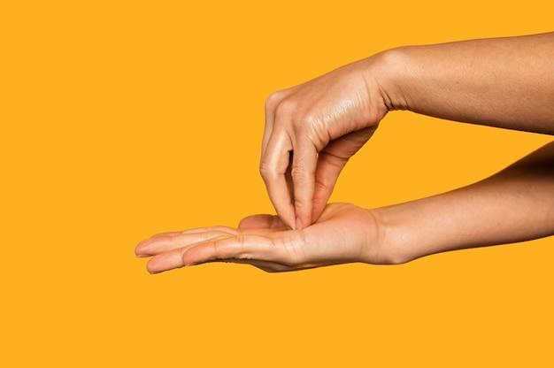 Zijwaarts persoon handen wassen geïsoleerd op oranje