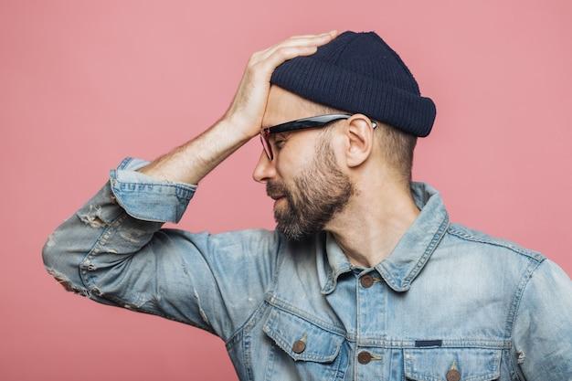 Zijwaarts portret van een bebaarde man heeft spijtige uitdrukking, houdt de hand op het voorhoofd