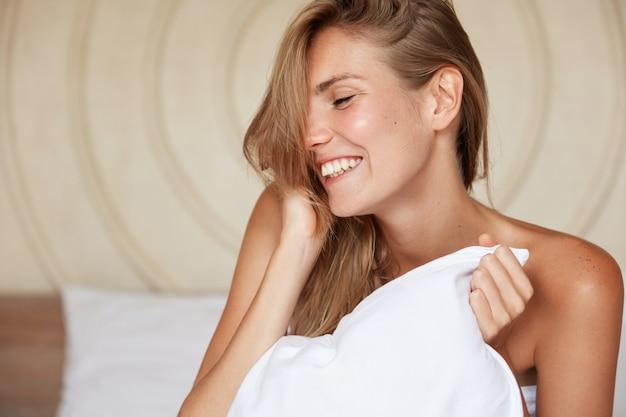 Zijwaarts portret van gelukkige vrouw wakker in goed humeur na een gezonde droom 's nachts, zit op een comfortabel bed met kussen. ontspannen vrouw vormt in slaapkamer of hotelkamer met vrolijke uitdrukking