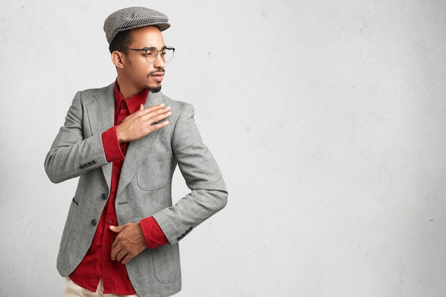 Zijwaarts portret van intelligente mannelijke onderzoeker of wetenschapper draagt pet, rood shirt en formele jas,