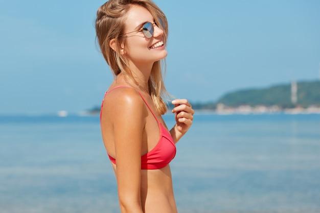 Zijwaarts portret van slanke, gelukkige jonge vrouw draagt rode zwembroek en zonnebril, overweegt prachtig uitzicht, heeft goede vakanties op onbekende exotische plek.