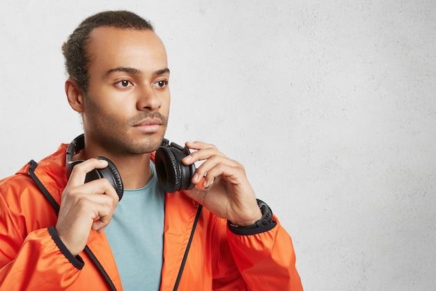 Zijwaarts portret van stijlvolle hipster man met donkere huid, koptelefoon houdt