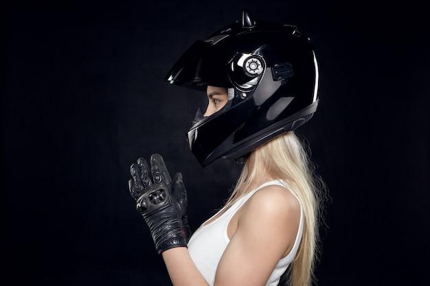Zijwaarts portret van trendy uitziende jonge vrouw motorrijder met gespierde schouders