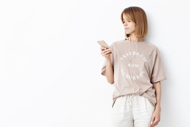 Zijwaarts portret van vrouwelijke student die na lessen thuis rust, probeert te ontspannen na hard werken, popmuziek luisteren met oortelefoons, moderne mobiele telefoon gebruiken om internet te zoeken