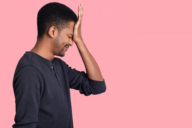 Zijwaarts realiseert de mens zijn fout, houdt de hand op het voorhoofd, gekleed in vrijetijdskleding, heeft spijt van iets, gekleed in een casual trui, geïsoleerd op een roze muur met lege ruimte voor uw tekst