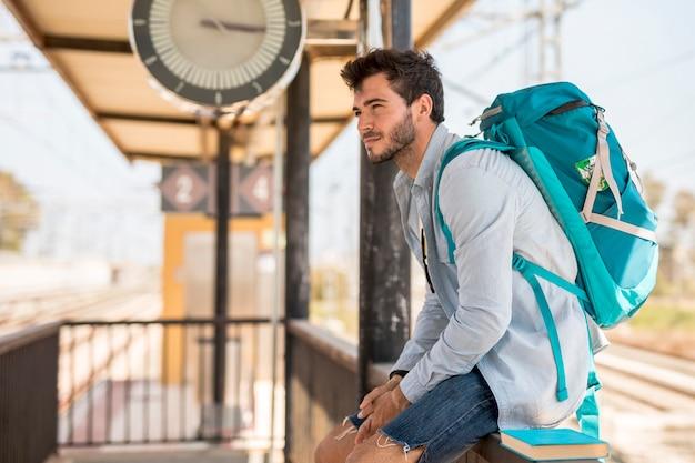Zijwaarts reiziger die op trein wacht