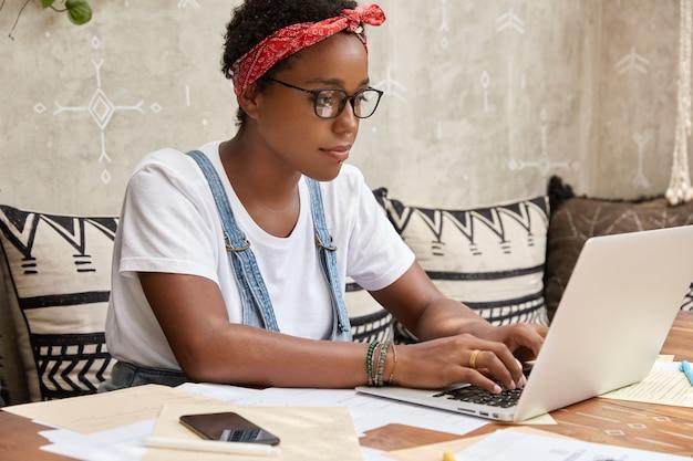 Zijwaarts schot van donkere huidskleurige werkneemster heeft zaken online, toetsenborden op laptopcomputer