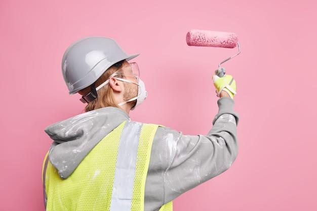 Zijwaarts schot van drukke klusjesman gekleed in veiligheidsuniform houdt verfroller draagt beschermend masker werkt hard geïsoleerd over roze muur. reparatie en renovatie concept. onderhoudswerker.