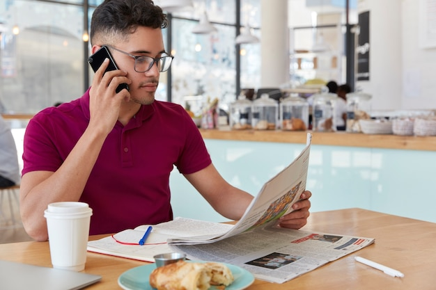 Zijwaarts schot van geconcentreerde ondernemer leest zakenkrant, voert telefoongesprek, werkt op afstand vanuit een coffeeshop, praat via mobiel, drinkt afhaalkoffie, eet een dessert. massamedia concept