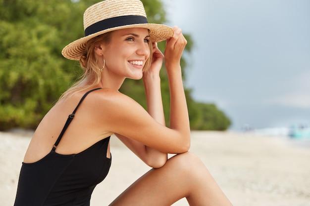Zijwaarts schot van gelukkige mooie jonge vrouwelijke toerist draagt zwarte badkleding en zomerhoed, zonnebaadt op het strand, bewondert prachtig uitzicht op de oceaan, heeft een positieve uitdrukking. mensen en recreatie concept