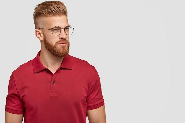 Zijwaarts schot van gember mannetje met trendy kapsel, dikke baard, opzij gericht, denkt aan nieuw project, draagt licht casual rood t-shirt, geïsoleerd over witte muur