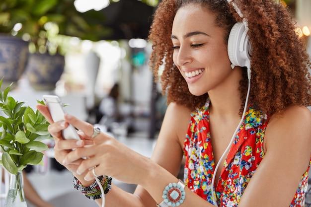 Zijwaarts schot van mooie jonge afro-amerikaanse vrouw controleert e-mail op slimme telefoon, luistert naar coole muziek uit de afspeellijst, gebruikt moderne koptelefoons