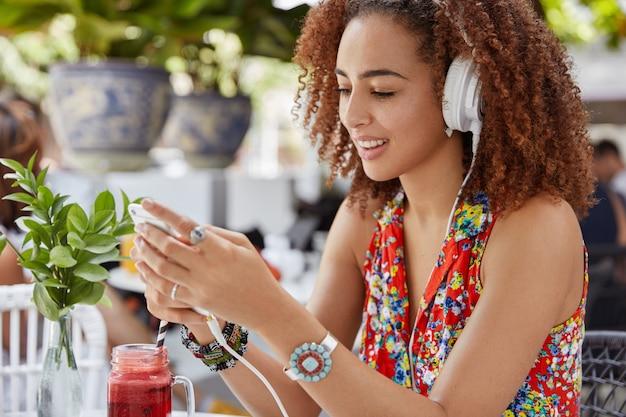 Zijwaarts schot van mooie opgetogen jonge vrouw heeft plezier en lacht terwijl favoriete compositie in koptelefoon luistert, bericht naar vriendje typt