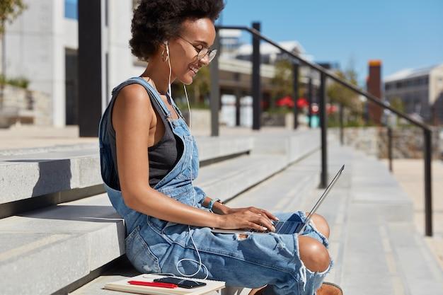 Zijwaarts schot van ontspannen, zorgeloze jonge dame met knapperig haar, luistert naar radio in oortelefoons, toetsenborden op laptopcomputer, doet freelance werk, dagboek in de buurt, zit op trappen tijdens zonnige dag boven uitzicht op de stad