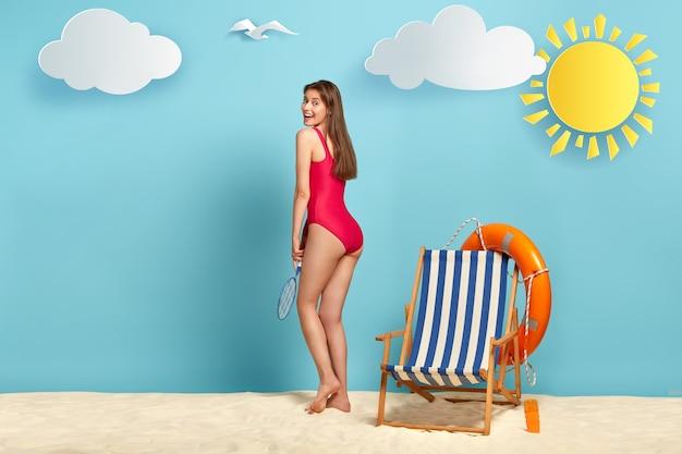 Zijwaarts schot van slanke positieve vrouw draagt rode zwembroek, houdt een tennisracket, heeft actieve rust op het strand, vrije tijd