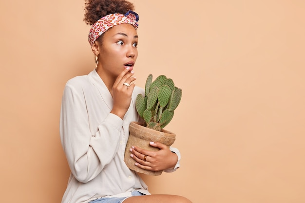 Zijwaarts schot van verraste vrouw staart onder de indruk houdt adem in houdt ingemaakte cactus voelt onder de indruk draagt hoofddoek vastgebonden over hoofd wit overhemd geïsoleerd over beige muur kopie ruimte