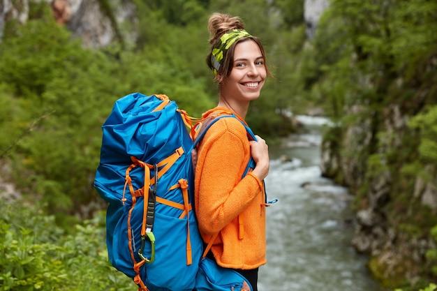 Zijwaarts schot van vrolijke vrouw in oranje trui, dwaalt in de buurt van bergrivier