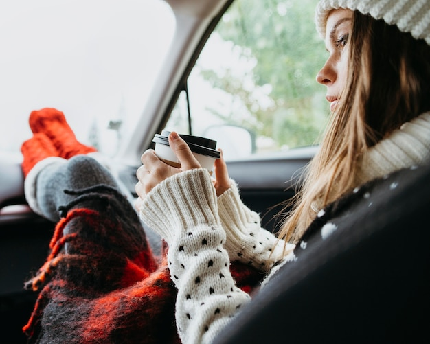 Zijwaarts vrouw zitten in een auto met een kopje koffie