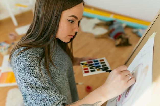 Zijwaarts vrouwelijk schilderij en haar werk