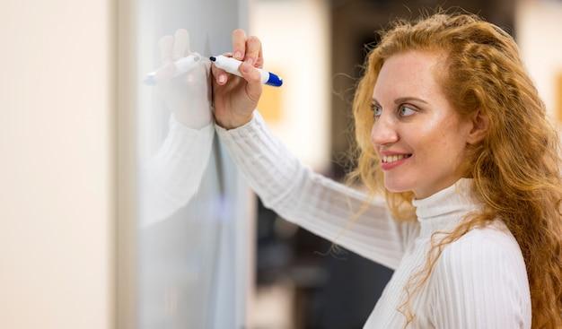 Zijwaarts zakenvrouw schrijven met een marker