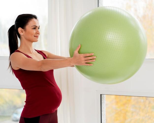 Zijwaarts zwangere vrouw die een groene geschiktheidsbal houdt