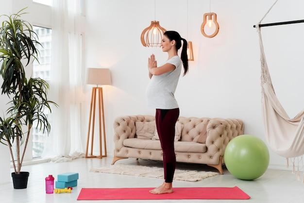 Zijwaarts zwangere vrouw die op geschiktheidsmat uitoefent