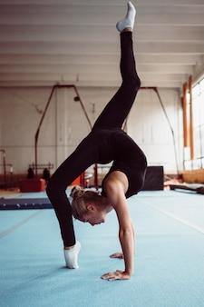 Zijwaartse blonde vrouw die voor gymnastiekkampioenschap opleidt