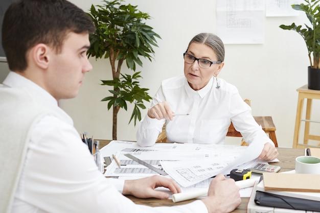 Zijwaartse foto van nerveuze jonge brunette mannelijke architect zittend aan een bureau met blauwdrukken, bang voelen terwijl boze vrouwelijke baas van middelbare leeftijd hem uitscheldt voor fouten in architectonisch plan