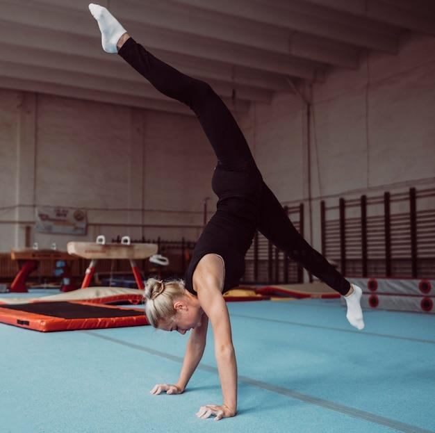 Zijwaartse jonge blonde vrouw die voor gymnastiekkampioenschap opleidt